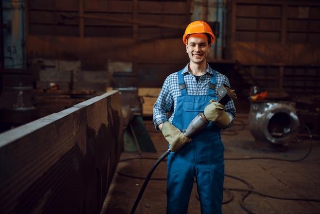 Рабочий в форме и шлеме работает с металлическими деталями на заводе. металлообрабатывающая промышленность, промышленное производство металлопродукции.