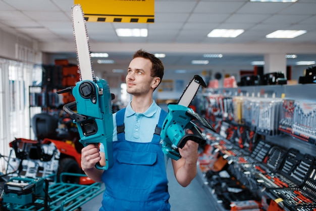 Рабочий в форме держит большие и маленькие бензопилы в магазине инструментов. выбор профессионального оборудования в строительном магазине, инструментальном супермаркете