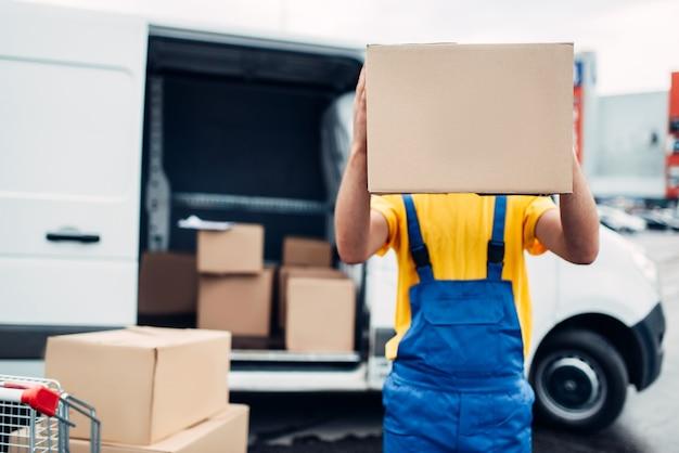Мужчина-работник в форме держит в руках картонную коробку, распределительный бизнес. доставка груза. пустой прозрачный контейнер