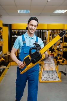 제복을 입은 남성 노동자는 도구 저장소에서 전기 톱을 보유하고 있습니다. 하드웨어 상점, 전기 기기 슈퍼마켓의 전문 장비 선택
