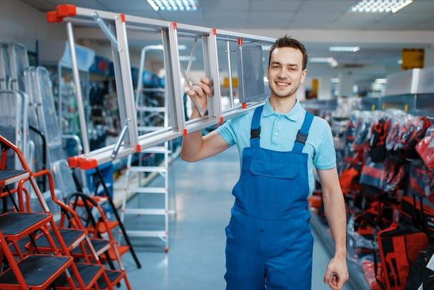 제복을 입은 남성 노동자는 도구 저장소에 새로운 알루미늄 접사 다리를 보유하고 있습니다. 사다리가있는 부서, 하드웨어 상점의 장비 선택, 악기 슈퍼마켓