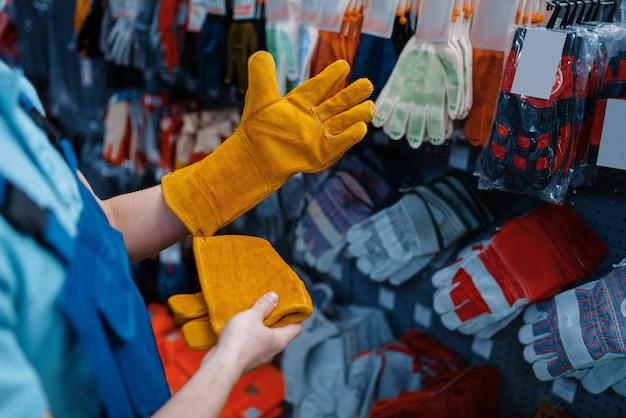 제복을 입은 남성 노동자는 도구 저장소에서 장갑을 끼고 있습니다. 하드웨어 상점, 악기 슈퍼마켓의 전문 장비 선택