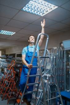 ツールストアの脚立に制服立っている男性労働者。はしごのある部門、金物店での機器の選択、楽器のスーパーマーケット