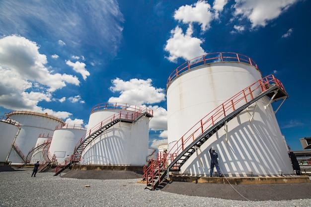 男性労働者産業目視検査貯蔵タンク油曇り青空。