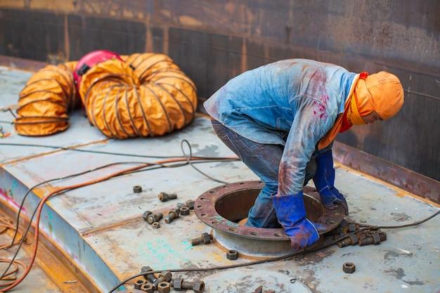폰툰 탱크 저장 육안 검사 탱크 내부의 남성 작업자는 밀폐 된 공간으로 송풍기 공기입니다.