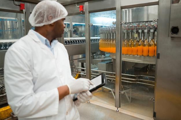 Lavoratore di sesso maschile che ispeziona le bottiglie di succo in fabbrica