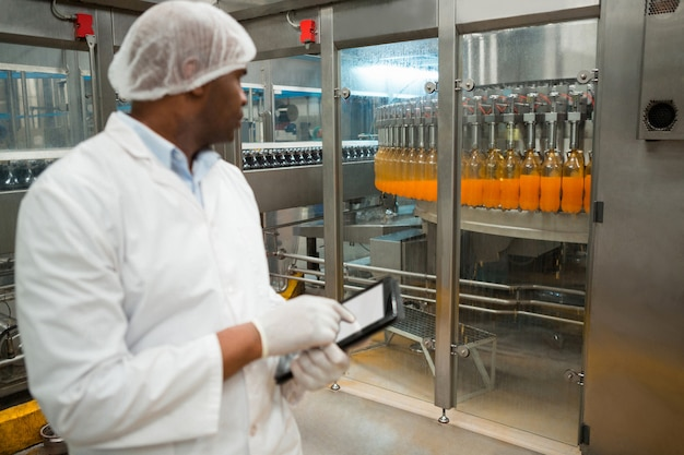 工場でジュースボトルを検査する男性労働者