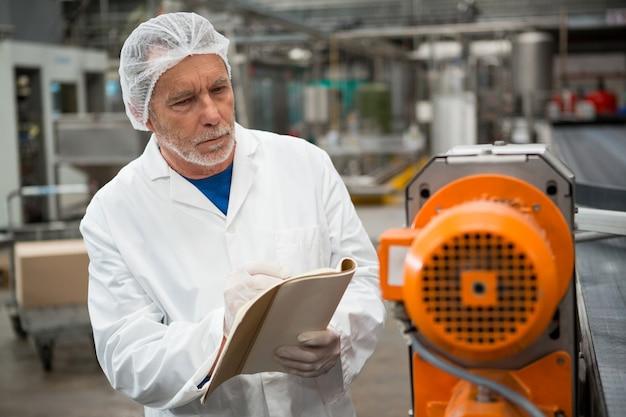 Мужчина-работник осматривает машины на заводе холодных напитков