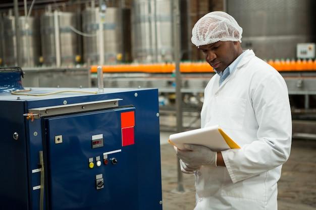 Мужчина-работник осматривает машины на фабрике соков
