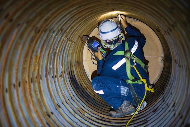 男性労働者の検査では、ボイラースキャンのコイルパイプの円形の厚さを危険な限られたスペースに測定しました。
