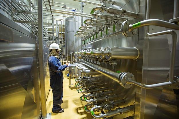 남성 작업자 검사 파이프라인은 식품 산업을 위해 액체 또는 우유 및 물을 펌핑하기 위한 시스템의 스테인리스 스틸 압력 튜브를 압력을 가합니다.