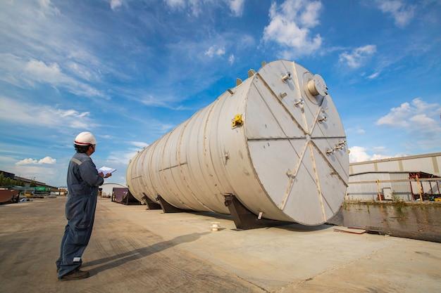 青空の工場で水平ステンレス鋼タンクを製造する男性労働者検査プロセスタンク