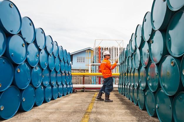 남성 작업자 검사 기록 드럼 오일 스톡 배럴은 업계에서 파란색과 녹색 수평 또는 화학 물질입니다.