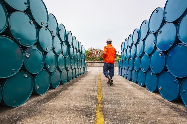 男性労働者の検査は、業界での青と緑の水平または化学薬品のドラムオイルストックバレルを記録します。