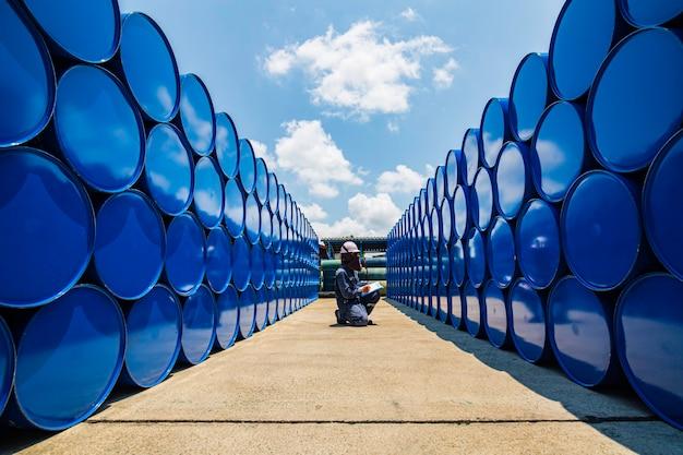 남성 작업자 검사 기록 드럼 오일 스톡 배럴은 업계에서 파란색 수평 또는 화학 물질입니다.