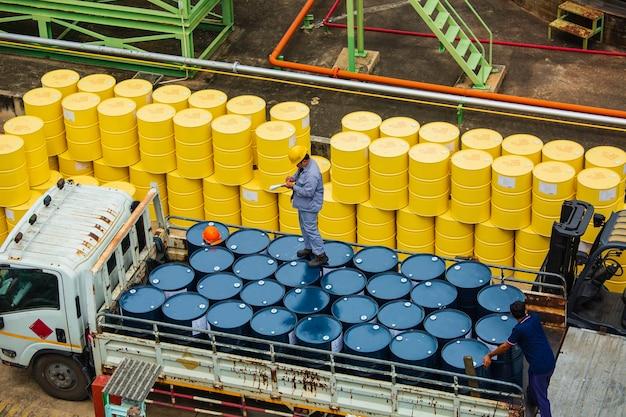 男性労働者の検査は、業界の輸送トラックの男性のための黄色と青の垂直または化学薬品のドラムオイルストックバレルを記録します。