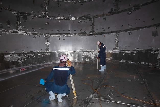 Мужской рабочий осмотр уровня обследования резервуара из нержавеющей стали в замкнутом пространстве