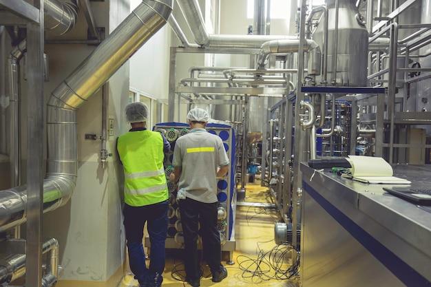 男性労働者が製造パイプラインとステンレスタンクで食品飲料のプロセスを検査