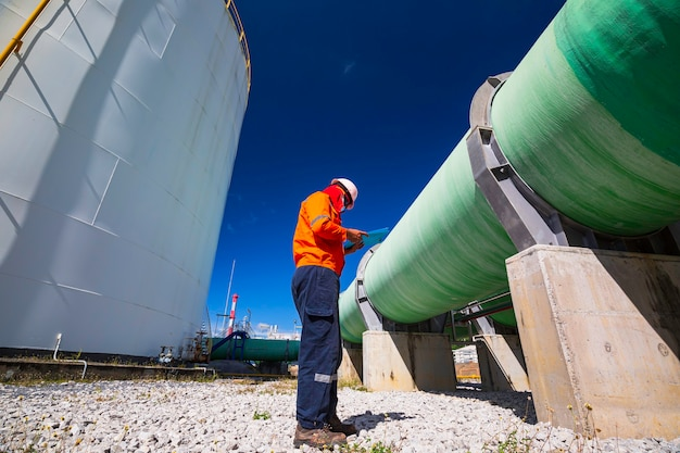 Male worker inspection visual big pipeline green power plant generates electricity water and gas.