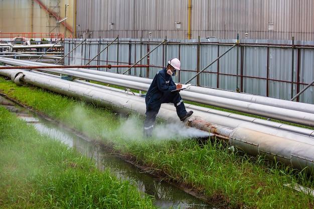 남성 작업자는 절연체에서 소켓 튜브 증기 가스 누출 파이프라인을 통해 시각적 파이프라인 오일 및 가스 부식 녹을 검사합니다.