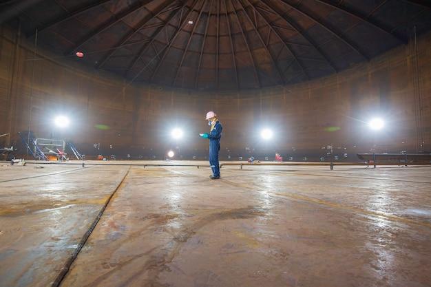 Мужчина-работник осмотр визуальный отчет черновой вариант резервуара стальной шов днища масла с точечным освещением внутренние ограниченные характеристики