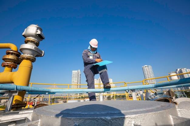 男性労働者検査視覚屋根貯蔵タンクオイル背景都市と青空