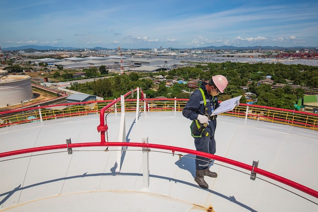 남성 작업자 검사 시각적 지붕 저장 탱크 오일 배경 도시와 푸른 하늘.