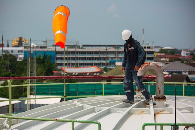Male worker inspection visual roof storage tank oil windsock indicator of wind on tank chemical cone.