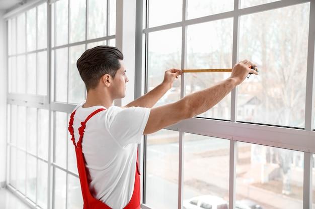 Работник-мужчина, устанавливающий окно в квартире