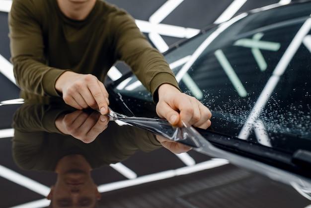 男性労働者は車のボンネットに透明な保護フィルムを取り付けます。自動車の塗装を傷から保護するコーティングの設置。ガレージの新車、チューニング手順