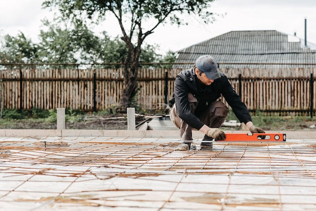 Male worker measures the construction level of rebar for the foundation of a house under construction