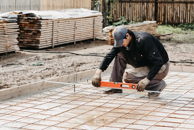 Male worker measures construction level of rebar for the foundation of a house under construction