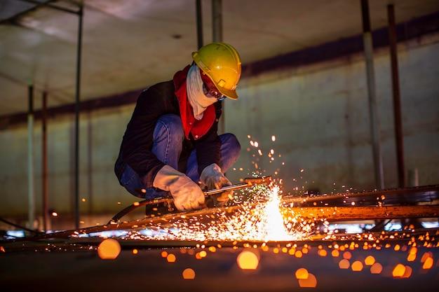 Искра резки металла рабочего мужчины на стальной пластине дна резервуара со вспышкой режущего света крупным планом в защитных перчатках и маске в ограниченном пространстве.