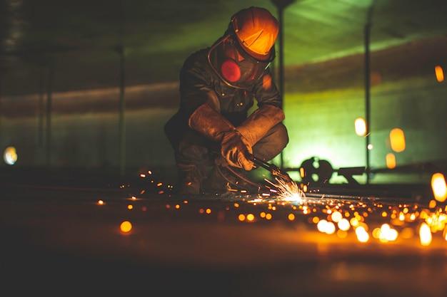 男性労働者の金属切断火花がタンク底部の鋼板にあり、カッティングライトのフラッシュがクローズアップされています。保護手袋とマスクを側面の限られたスペースに着用してください。