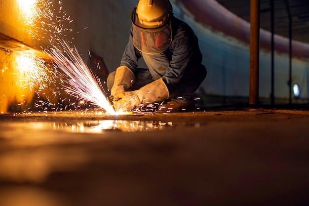 タンク底部の鋼板に男性労働者の金属切削火花があり、カッティングライトのフラッシュがクローズアップされ、側面の限られたスペースで保護手袋とマスクを着用します。