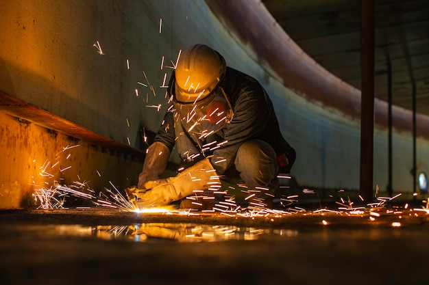 Male worker metal cutting spark on tank bottom steel plate with flash of cutting light close up wear protective gloves and mask in side confined space.