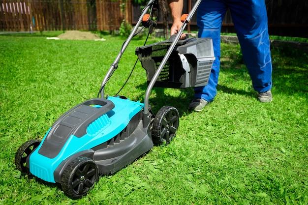 현대 잔디 깎는 기계의 도움으로 잔디를 깎는 작업 거리에 남성 노동자