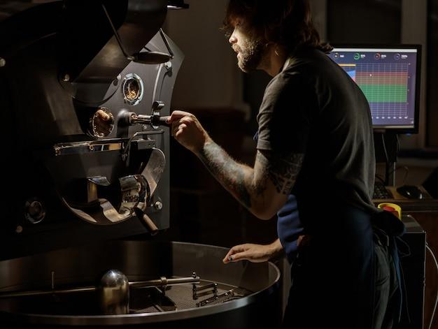 공장에서 커피 로스팅 기계를 작동하는 남성 노동자