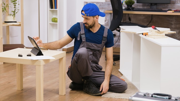 Male worker in overalls assembles new white furniture in new home owners. man reading instruction on laptop.