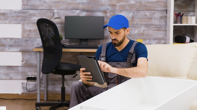 Male worker in overalls wearing a cap reading furniture assembly from a tablet computer.