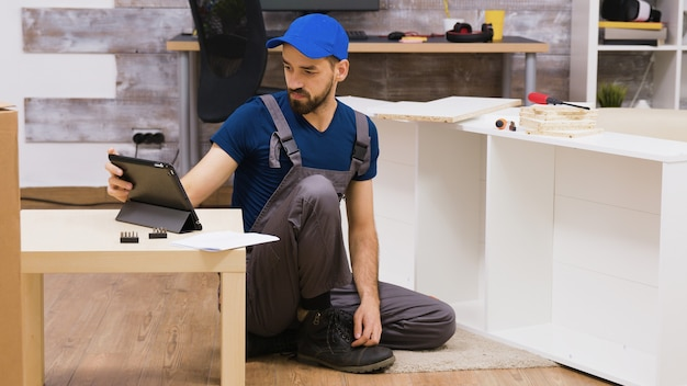 Male worker in overalls with a cap assembly a shelf in new home following insctruction from tablet computer
