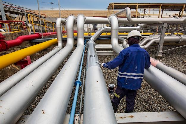 Мужчина-рабочий окрашен в серый цвет на трубопроводе, работающем над клапаном подачи нефти