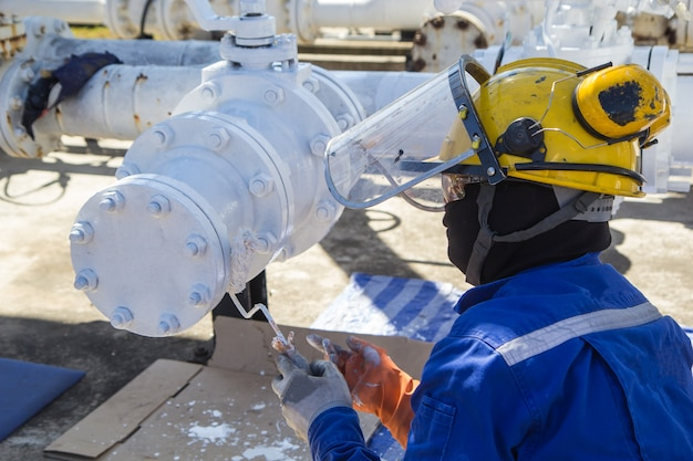 Male worker painted white at pipes and oil valve