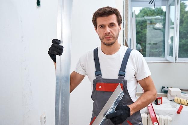 긴 주걱을 사용하여 벽을 석고 남성 노동자. 혁신 개념