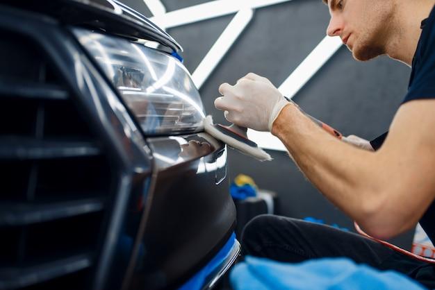 Рабочий-мужчина полирует передний бампер с помощью полировальной машины, крупным планом детализируя автомобиль.