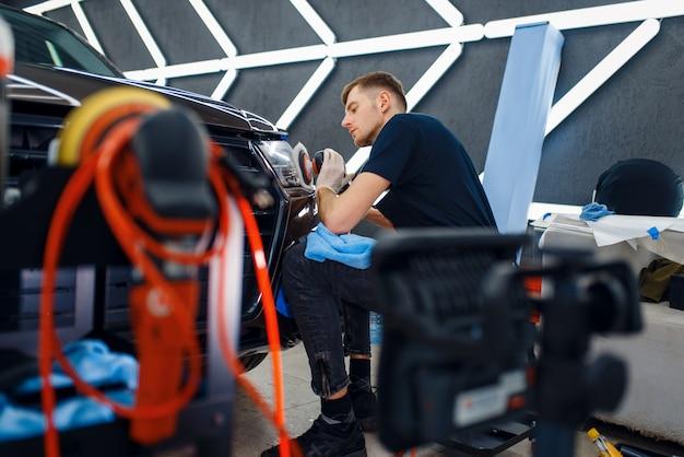 男性労働者がヘッドライト、車のディテールを磨く