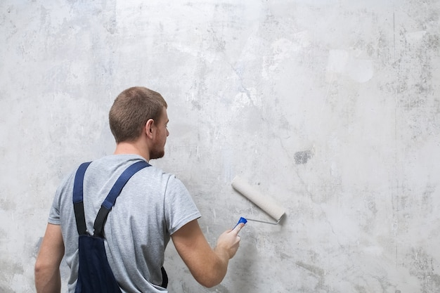 A male worker primes the wall with a roller for better grip