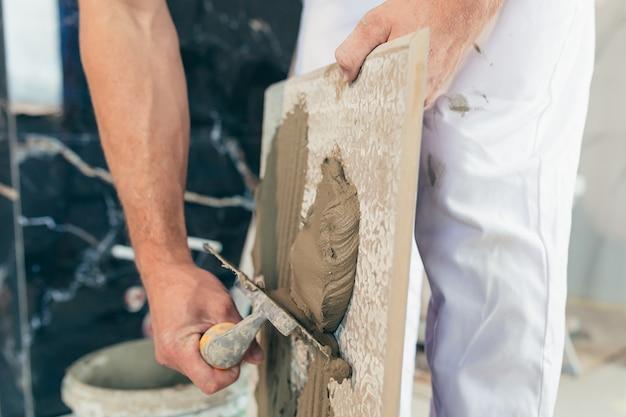 Мужчина-работник-профессионал монтирует керамическую плитку в ванной, фото с близким шпателем с клеем
