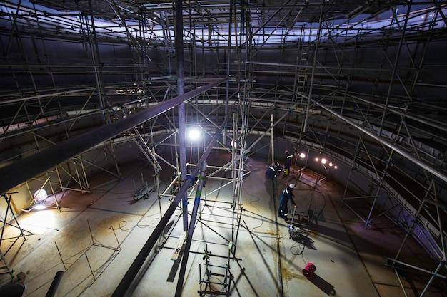 Male worker in progress tank oil inspection scaffolding in confined space