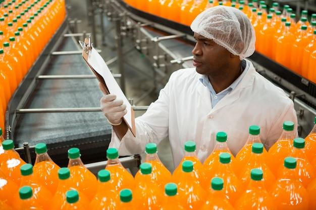 ジュース工場でボトルを検査しながらクリップボードを読んでいる男性労働者